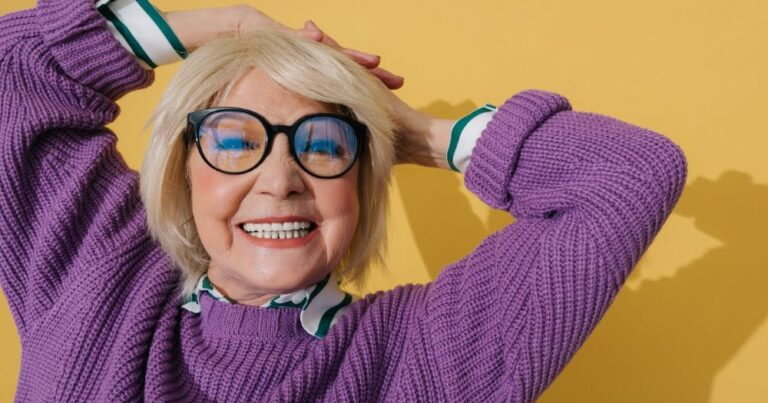 Smiling older woman wearing a purple sweater shows the possibility of aging gracefully