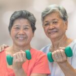Two asian women demonstrating the use of hand weights to prevent osteoporosis